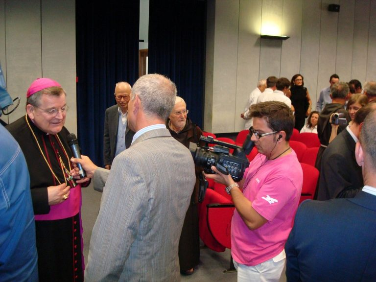 Cardinal Burke being interviewed by press at the collaboration program at the Casa Hospital in San Giovanni Rotondo, Italy